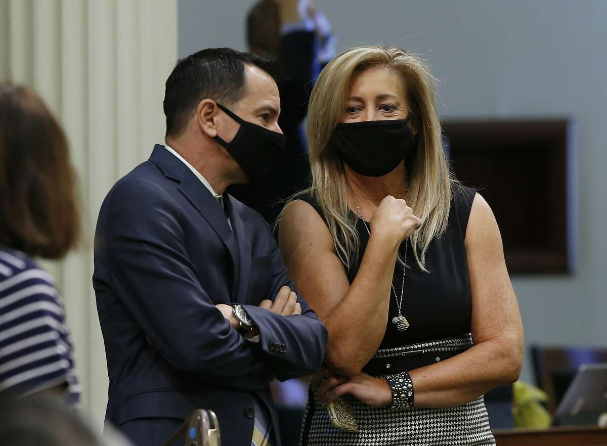 In this Wednesday, June 10, 2020, photo, Assembly Speaker Anthony Rendon, D-Lakewood, left, talks with Assembly Republican Leader Marie Waldron, of Escondido, during the Assembly session in Sacramento, Calif. Lawmakers will meet Monday, June 15 to pass their version of the state budget. But the budget will likely change as negotiations continue with Gov. Gavin Newsom on how to cover a $54.3 billion deficit. (AP Photo/Rich Pedroncelli)