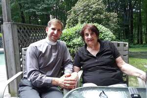 Linda Figlewski sits at her Harwtinton home with her son, the Rev. Brett Figlewski.
