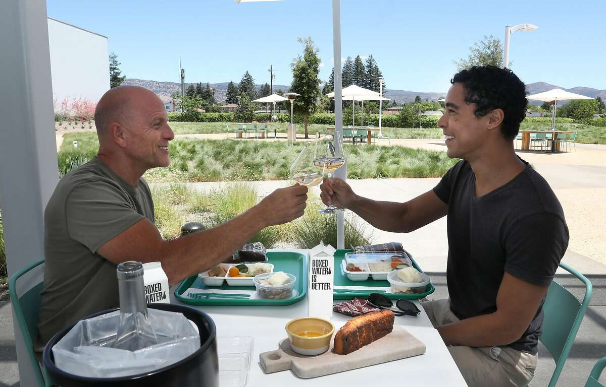 Member Greg Gregory (left) from Napa and Deray Parker (right) from San Francisco meet to have wine and focaccia bread at Ashes & Diamonds winery on Tuesday, June 16, 2020, in Napa Calif.