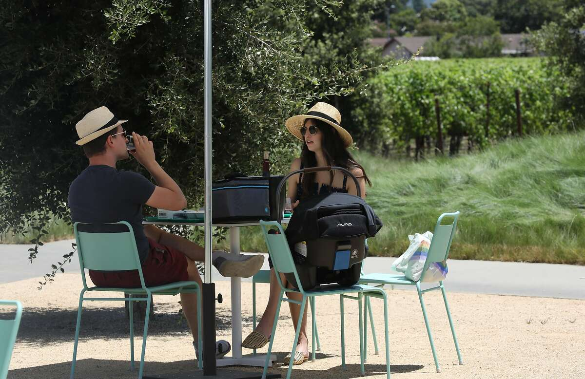 Brian Lerner (left) and Perri Lerner (right) from San Francisco have a picnic and wine tasting at Ashes & Diamonds winery with their newborn on Tuesday, June 16, 2020, in Napa, Calif.