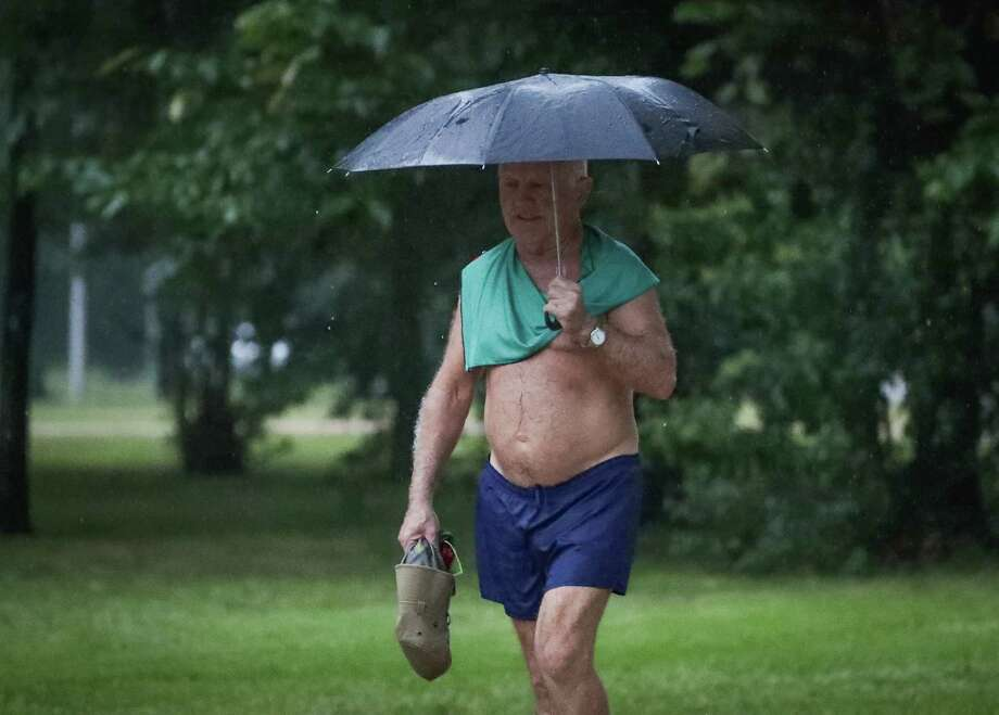 Seventy-four-year-old former marathon runner, Mike Chewey, enjoyed his rain workout in Memorial Park with the aid of an umbrella Monday, June 22, 2020, in Houston. Photo: Steve Gonzales, Staff Photographer / © 2020 Houston Chronicle