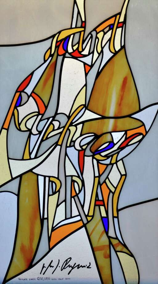 "Each of the stained glass windows at the Chapel of the Holy Spirit, on the campus of Sacred Heart University in Fairfield, features a modernist design with splashes of color in which words (rather than images) are interwoven referencing the people and events in the story of salvation. This ""Saint Raphael Pray for us"" window is signed by he artist, the Rev. Marko Rupnik of Rome. Photo: ST"