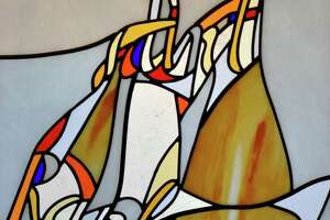 "Each of the stained glass windows at the Chapel of the Holy Spirit, on the campus of Sacred Heart University in Fairfield, features a modernist design with splashes of color in which words (rather than images) are interwoven referencing the people and events in the story of salvation. This ""Saint Raphael Pray for us"" window is signed by he artist, the Rev. Marko Rupnik of Rome."