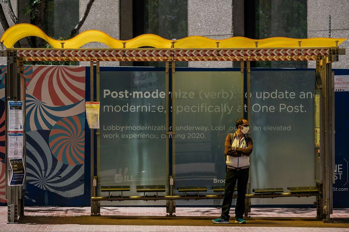 A public health banner displaying the requirement that masks be worn is seen on the side of a MUNI bus as a man wearing a mask passes by the other side in downtown San Francisco on Thursday, May 21, 2020.
