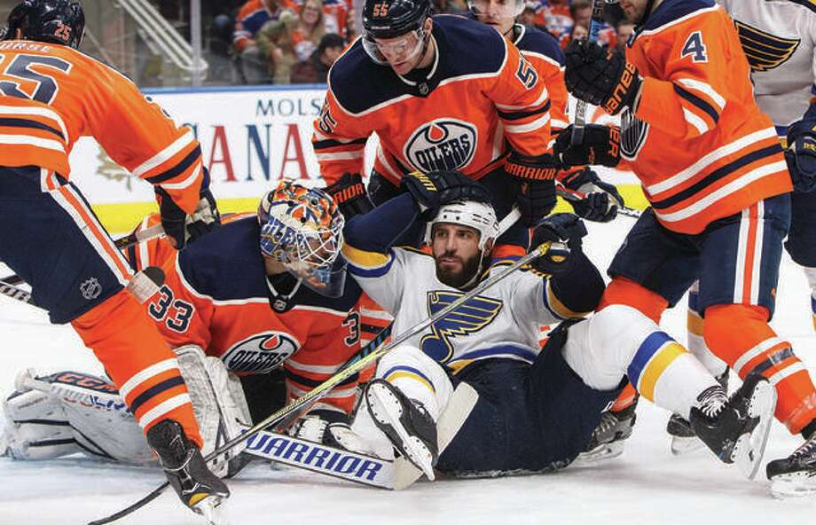 The Blues' Chris Thorburn (middle) crashes into Oilers goalie Cam Talbot during a 2017 game in Edmonton, Alberta. Thorburn announced his retirement Monday. Photo: AP Photo