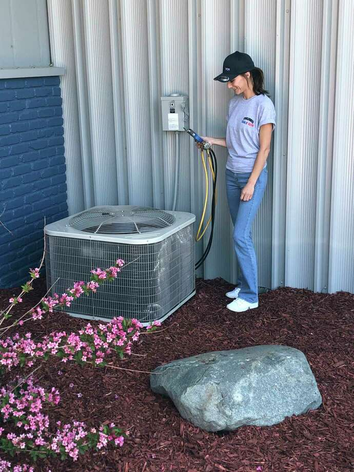 A Thumb Cooling and Heating technician works on an outdoor air conditioner. (Courtesy Photo)