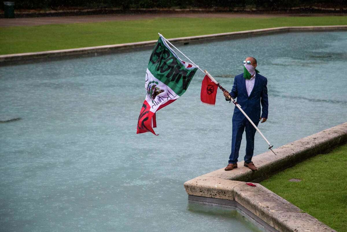 A demonstrator protests in front of the Houston City Hall with a flag with one side the Mexican flag design and the other the United States flag for a peaceful manifestation on Saturday, June 20, 2020, in Houston in support of the immigrants detained by ICE.