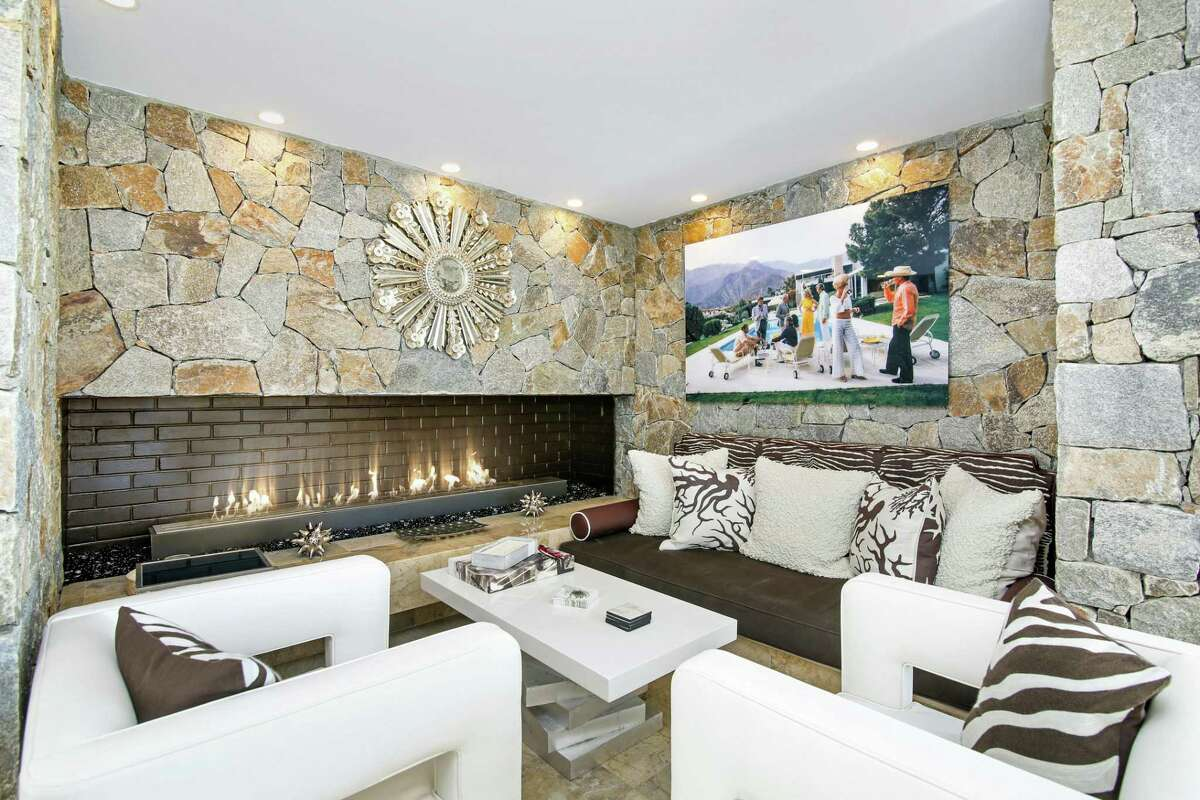The stone wall with the fireplace in the family room creates a comfortable sitting alcove.