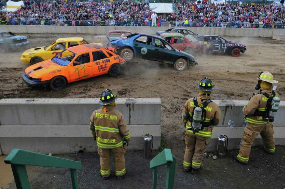 West Fort Ann firefighters stand by Monday night as the second heat of the Demolition Derby gets under way at the Washington County Fair in Greenwich.  ( Philip Kamrass / Times Union ) Photo: Philip Kamrass