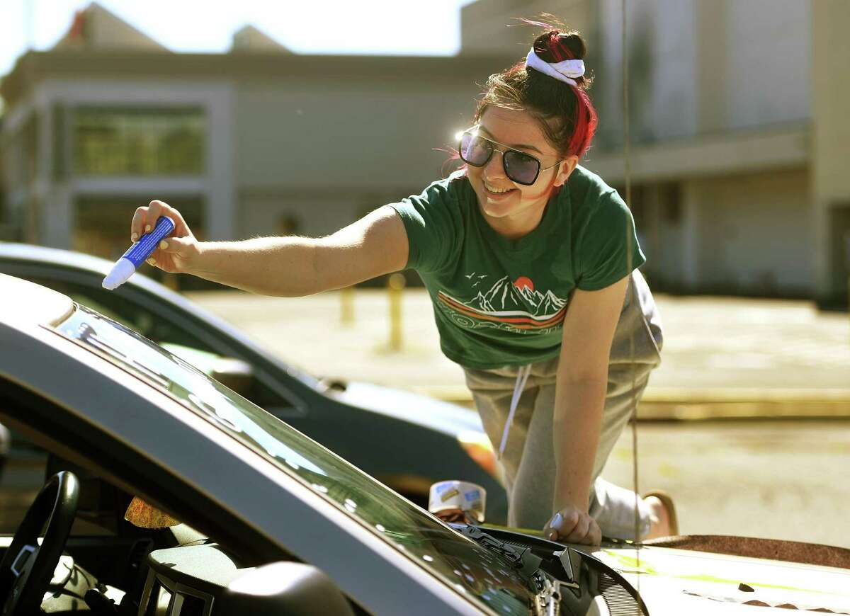 Trumbull High School 2020 graduate Kristina Franco decorates the windshield of her car for the Trumbull Eagles FlyThru street procession from the Westfield Trumbull Mall in Trumbull, Conn. on Sunday, June 21, 2020.