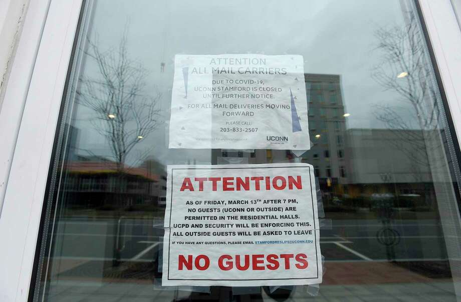 Signs posted, shown in a photograph taken on March 25, 2020, on the entrance way to UCONN Stamford's Residential Life building informs students of the changes in visitor policies, in response to the Covid-19 crisis. The building houses over 600 students who attend the university in Stamford, Connecticut. Universities across the state, having moved classes on line and sent students home due to the coronavirus, are in the process of figuring out a plan to reconcile with parents and students over room and board payments. Photo: Matthew Brown / Hearst Connecticut Media / Stamford Advocate