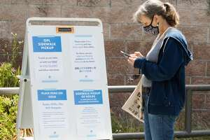A patron follows the instructions on how to pick up their book order at the Rockridge library in Oakland, Calif. on June 20, 2020. Oakland Libraries started pickup services for patrons at several branches, including the Rockridge branch of the Oakland Public Library.