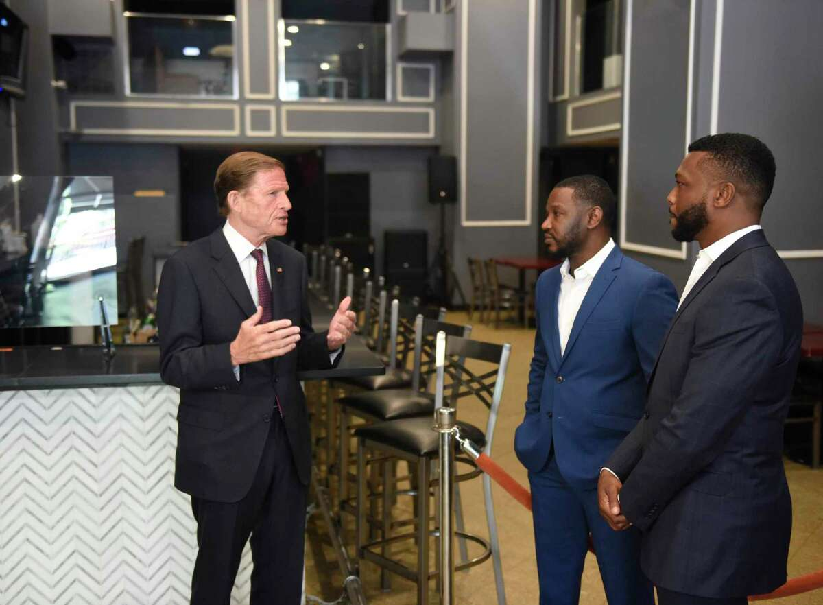 U.S. Sen. Richard Blumenthal, D-Conn, left, visits Caribbean-American restaurant La Perle to chat with co-owners Smith St. Juste, center, and Peter Medoit in downtown Stamford on Monday.