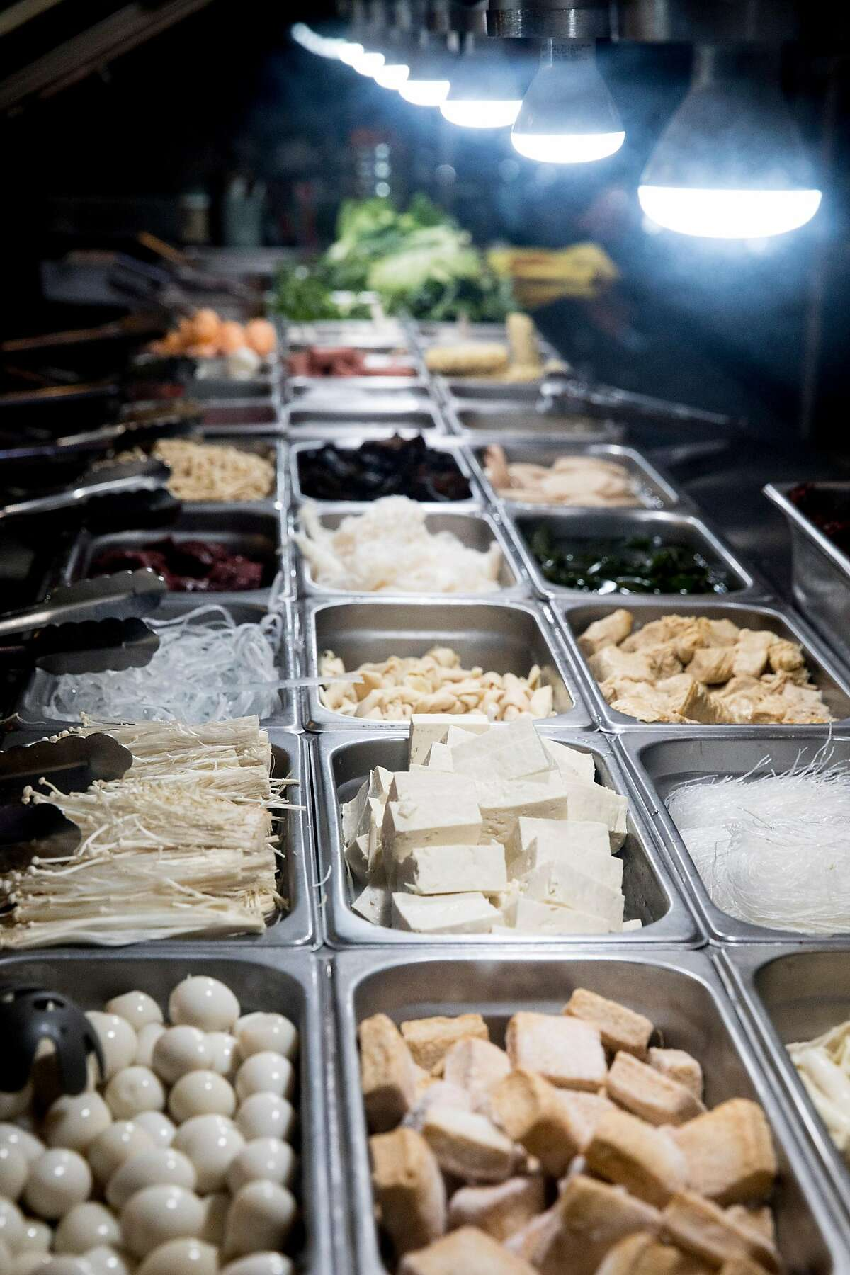 An assortment of vegetables, proteins and other ingredients sit out for customers to build their own meal base at Customize Malatang in Newark, Calif. Friday, Dec. 27, 2019.
