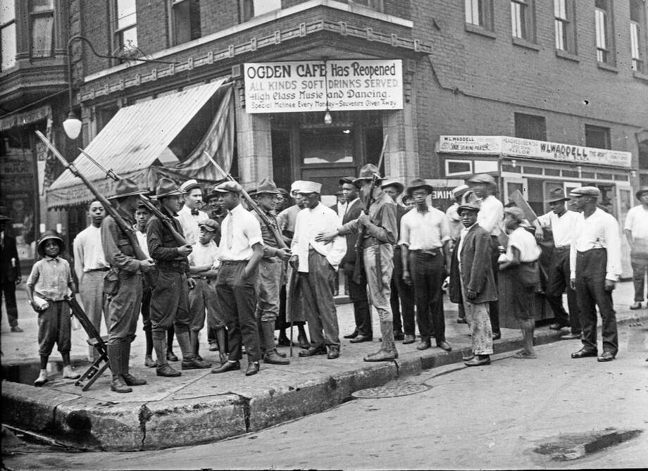 In this 1919 photo provided by Chicago History Museum, a crowd of men and armed National Guard stand in front of the Ogden Cafe during race riots in Chicago. Red Summer, as the summer of 1919 came to be known, saw white-on-black violence in big cities like Washington and Chicago and small towns like Elaine, Ark., and Bisbee, Ariz. (Chicago History Museum/The Jun Fujita negatives collection via AP) Photo: Associated Press / No known copyright restrictions.