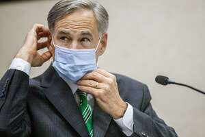Texas Gov. Greg Abbott adjusts his mask during a recent coronavirus updates. He made the right call in mandating masks.
