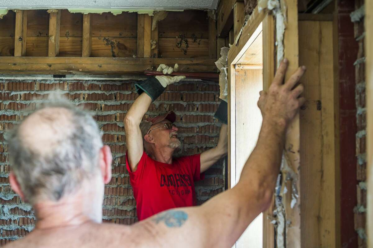 Joe Bennett of Merrill, center, assists his friend, CJ's Hairstyling co-owner Kim Methner, left, as they make repairs to the damaged building Monday, June 22, 2020 in downtown Sanford. (Katy Kildee/kkildee@mdn.net)