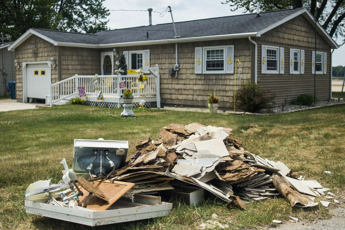 Debris and damaged items are set out to the curb on Island Drive Monday, June 22, 2020 in Tobacco Township. (Katy Kildee/kkildee@mdn.net)