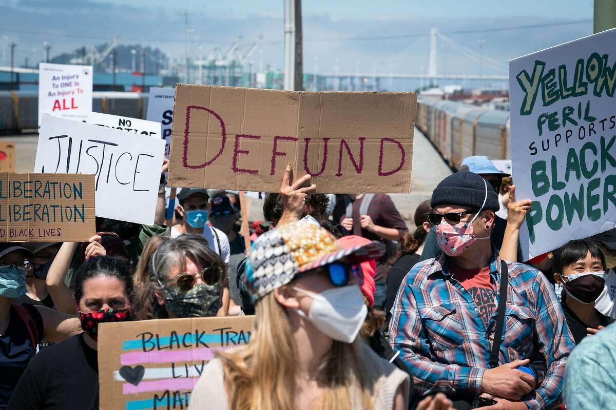 People march with signs demanding to defund the police, during a Juneteenth protest in Oakland, Calif., on Friday, June 19, 2020.