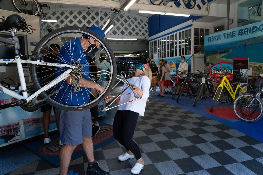 Owner Jeff Sears works on a bike aided by a laughing Annie Clauss, Blazing Saddles' vice president. Photo: Paul Kuroda / Special To The Chronicle