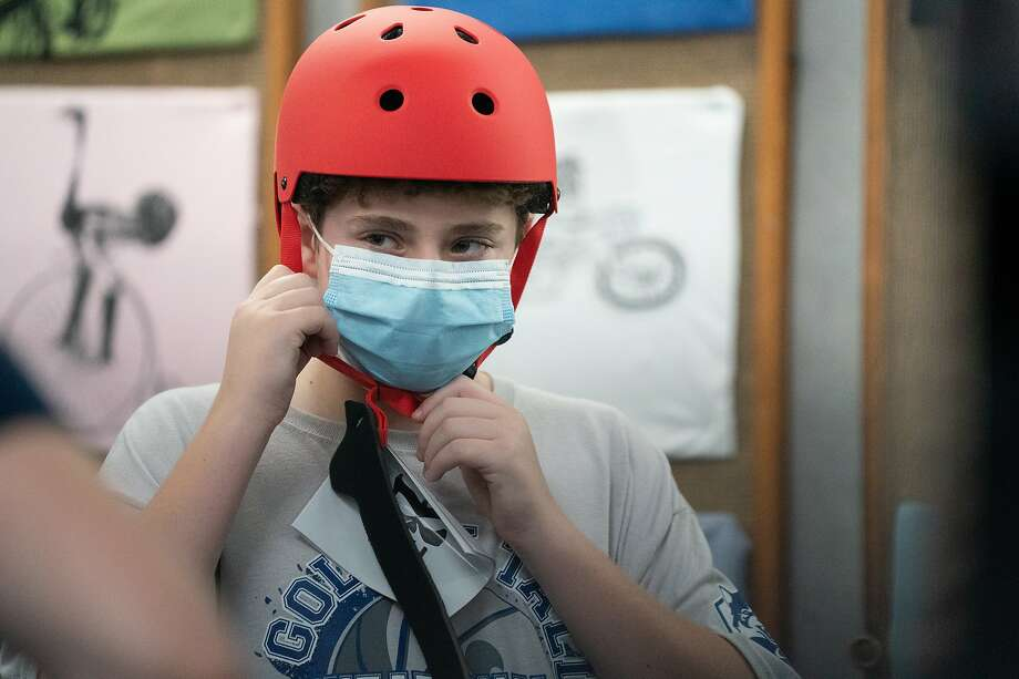 Solly Bobrowsky, 13, tries on a new helmet to go with his bike bought at the longtime rental store. Photo: Paul Kuroda / Special To The Chronicle