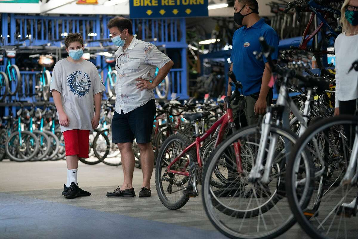 Solly Bobrowsky, 13, discusses with his dad, David, about purchasing a used bike at Blazing Saddles, a long-time bike rental store that now is meeting demand by selling them on Monday, May 25, 2020, in San Francisco, Calif.