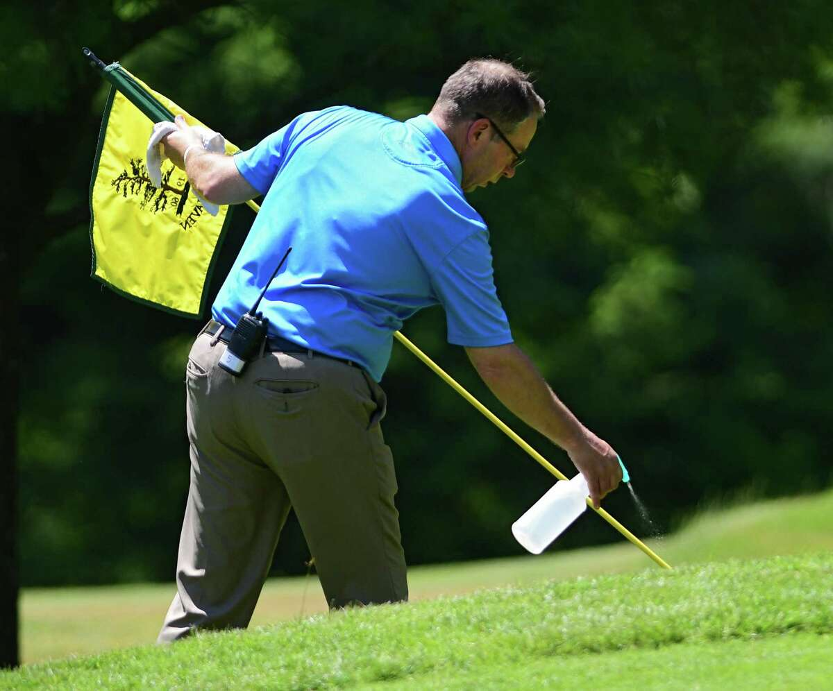 Tournament Director Doug Evans wiped down the flag on one of the greens during the Northeastern New York PGA Pro Classic 3 at Pinehaven Country Club on Monday, June 22, 2020 in Guilderland, N.Y. (Lori Van Buren/Times Union)