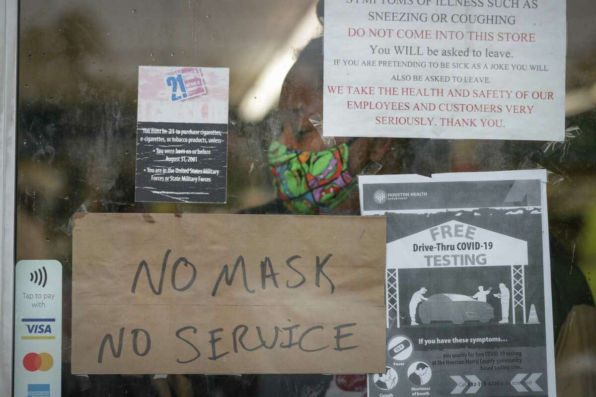 A sign on Ralston Discount Liquor door had signs informing patrons that Harris County Judge Lina Hidalgo has issued an order mandating that businesses in the county must require customers wear masks to slow the spread of the novel coronavirus Monday, June 22, 2020, in Houston. Employees and customers over the age of 10 must wear a mask or face covering, stay 6 feet apart from other customers and staff, and cannot enter a business if they are feeling ill.