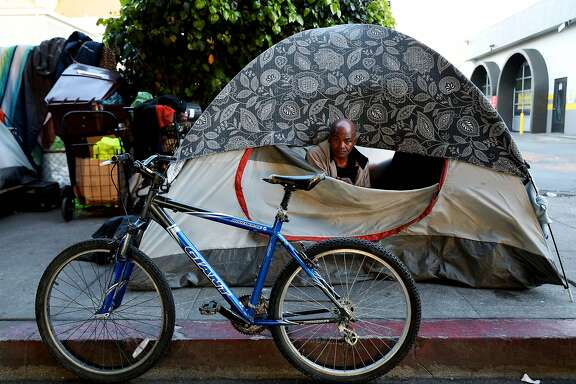 Larry Greer, 56, poses for a portrait from his tent on MLK Jr. Way in Oakland, Calif., on Thursday, March 26, 2020. �I never considered a shelter,� Greer said. �It�s my duty as a husband to take care of my family. And our time is coming. I believe in Hebrews 11:1 � �Now faith is the substance of things hoped for, the evidence of things not seen.�