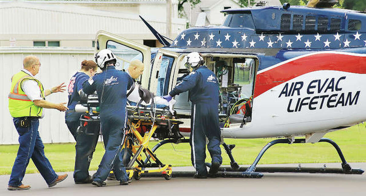 Emergency workers, including Hamel firefighters and flight nurses from Air Evac Lifeteam, load a pregnant woman onto an air medical ambulance Monday to be transported to Barnes-Jewish Hospital in St. Louis. The woman was in a Hyundai Entourage minivan that crashed into a landscaping truck on Illinois Route 140 at Staunton Road on the west side of Hamel early Monday afternoon.