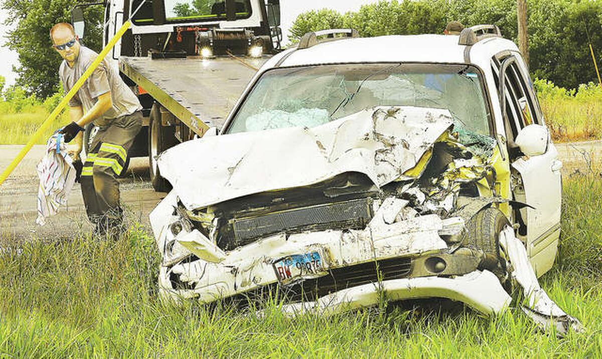 A tow truck operator cleans up debris around the minivan, which had heavy front-end damage and ended up off the road at the edge of a farmer's field.