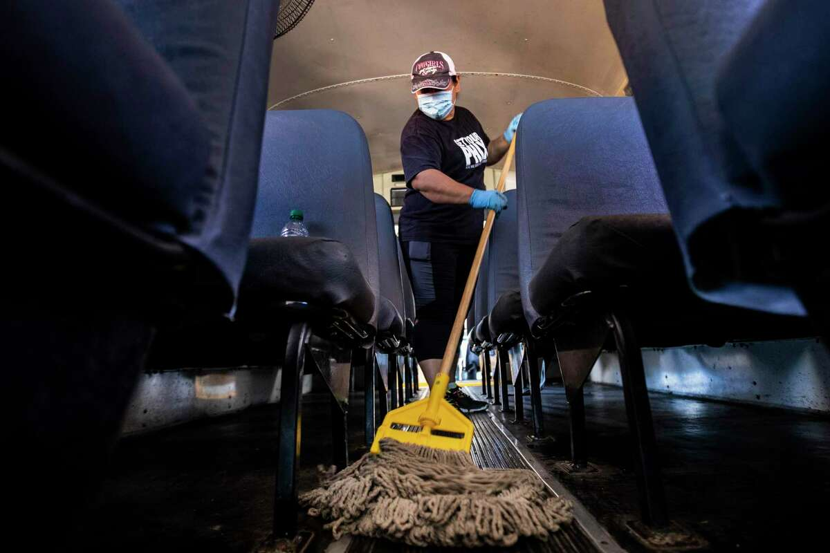 Humble ISD staff member Marlene Caballero mops the floor of a Humble ISD school bus on Thursday, June 11, 2020, in preparation for the opening of schools.