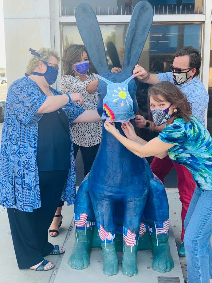 Monica Tschauner (wearing black and white), Leslie Gillian (wearing blue), Odessa Arts Executive Director Randy Ham and Connection Christian Church pastor Dawn Weaks placed masks on Jackrabbit sculptures on Monday in downtown Odessa. Photo: Courtesy Photo