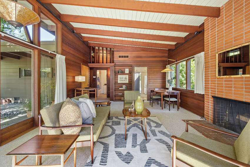 The original hearth stands ready to warm the space created by the vaulted ceiling.The mid-century wood paneling and brick are all preserved.