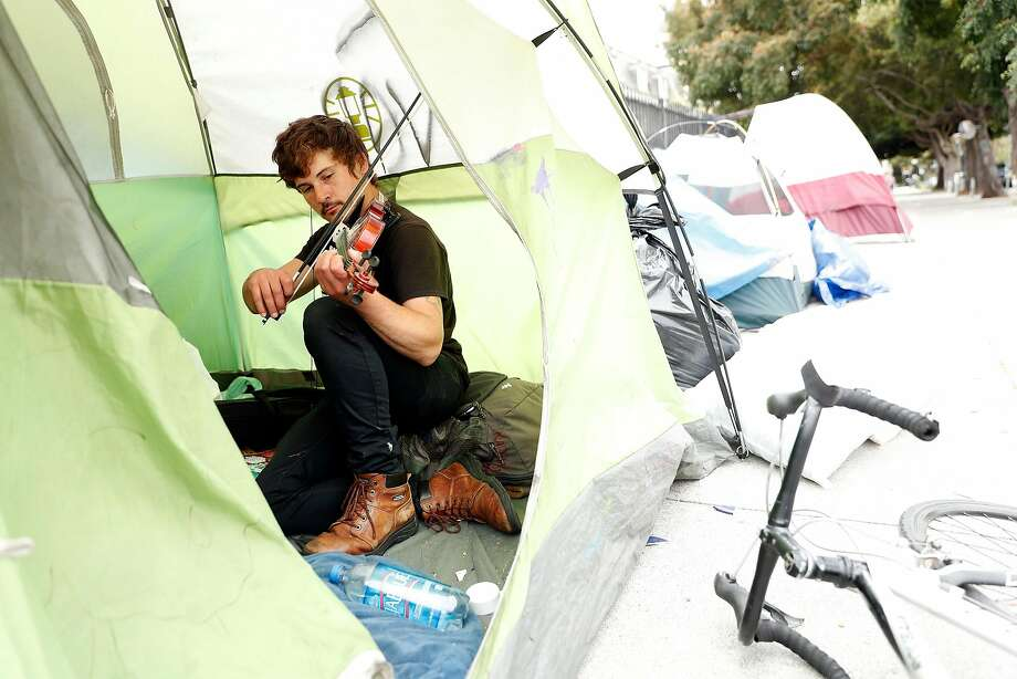 Rook, who is from Chicago and has been living on the street in San Francisco for two years, plays a violin in a friend's tent on Dolores Street. Photo: Scott Strazzante / The Chronicle