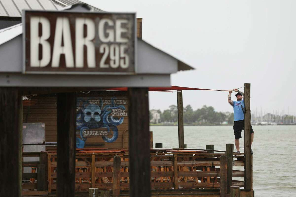 Jeff Schafer, general manager at Barge 295, hangs a sail that was blown loose during a thunderstorm Monday, June 22, 2020, at Barge 295 in Seabrook. The Texas Alcoholic Beverage Commission over the weekend suspended alcohol permits at a dozen bars, including two in the Houston area, as part of a statewide crackdown to enforce Gov. Greg Abbott's COVID-19 business restrictions. Barge 295 was issued a 30-day permit suspension for not implementing proper protocols to slow the spread of the virus.
