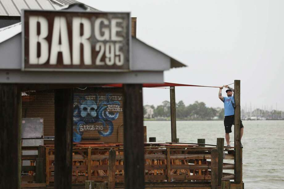 Jeff Schafer, general manager at Barge 295, hangs a sail that was blown loose during a thunderstorm Monday, June 22, 2020, at Barge 295 in Seabrook. The Texas Alcoholic Beverage Commission over the weekend suspended alcohol permits at a dozen bars, including two in the Houston area, as part of a statewide crackdown to enforce Gov. Greg Abbott's COVID-19 business restrictions. Barge 295 was issued a 30-day permit suspension for not implementing proper protocols to slow the spread of the virus. Photo: Jon Shapley, Staff Photographer / © 2020 Houston Chronicle