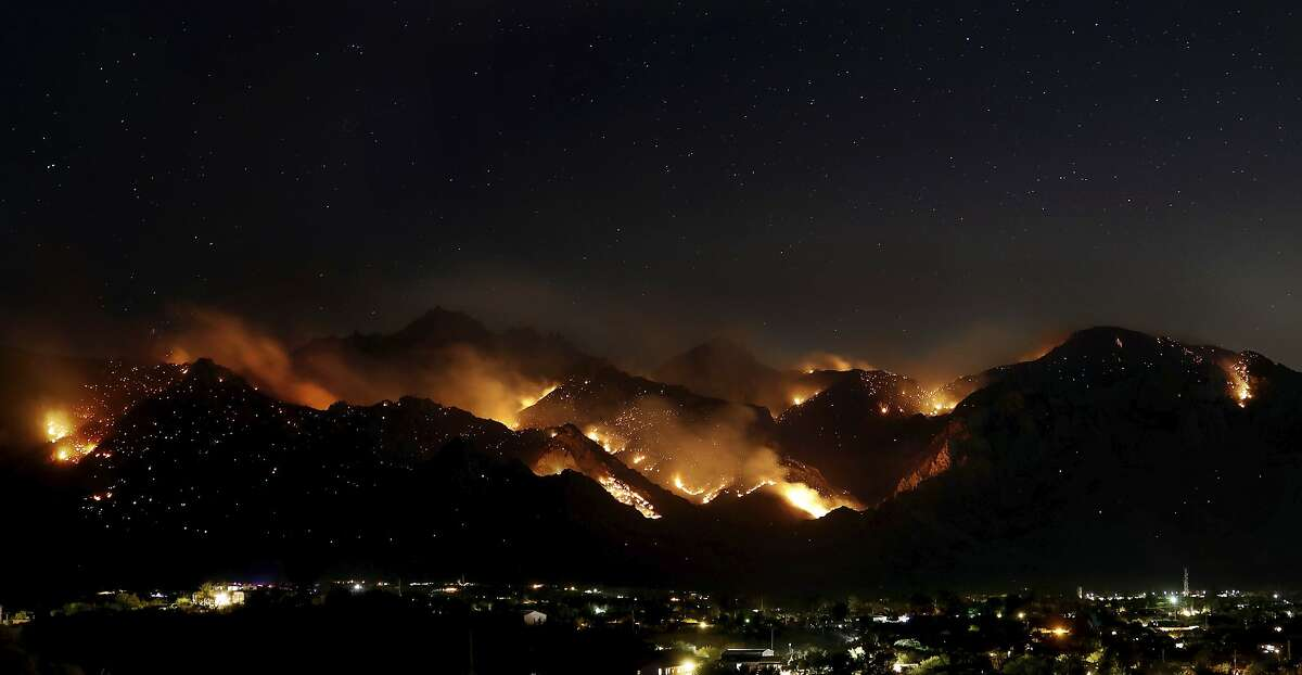 The Bighorn Fire burning in the wilderness of the Santa Catalina Mountains looms over homes as seen from Oro Valley, Ariz., Saturday, June 13, 2020. The fire has grown and is now threatening Mt. Lemmon and the town of Summerhaven, Ariz. (Kelly Presnell/Arizona Daily Star via AP)