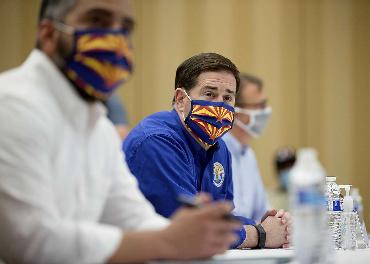 Gov. Doug Ducey, center, receives a briefing at the Incident Command Center inside the Hilton El Conquistador Resort in Tucson, Ariz., regarding wildfires across the state including the Bighorn Fire burning in the Santa Catalina Mountains on Monday, June 22, 2020. (Mamta Popat/Arizona Daily Star via AP)