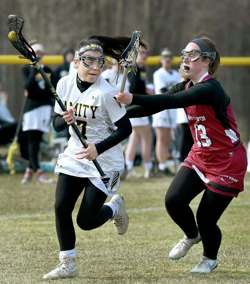 Payton Papa of Amity, left, runs down field against Quinn Kirby of North Haven on during the first half of girls lacrosse at Amity in Woodbridge on April 2, 2019. Photo: Peter Hvizdak / Hearst Connecticut Media / New Haven Register