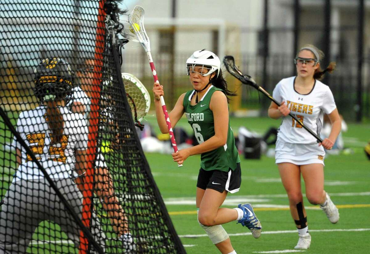 Guilford's Catherine Larrow (16) drives to the goal during girls lacrosse action against Daniel Hand in Madison on May 2, 2019.