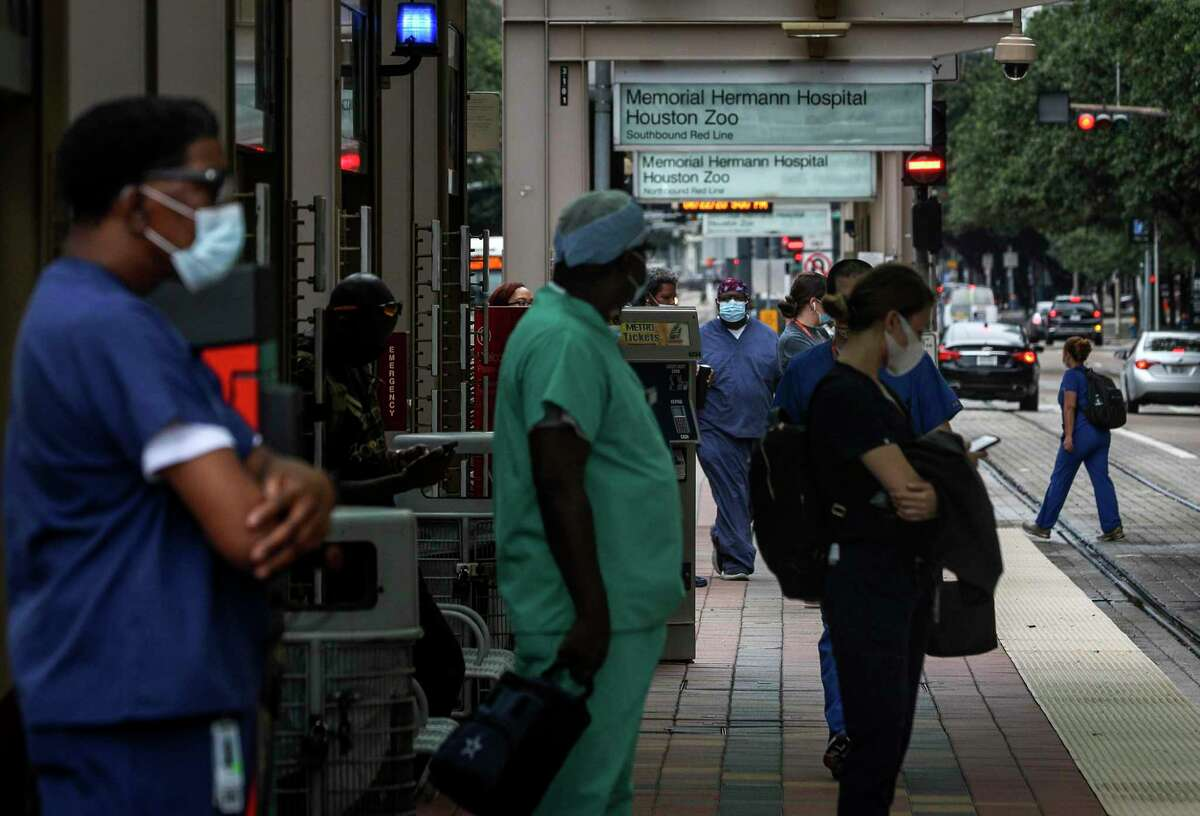 Medical workers wait to ride the light rail Monday, June 22, 2020, at the Texas Medical Center in Houston.