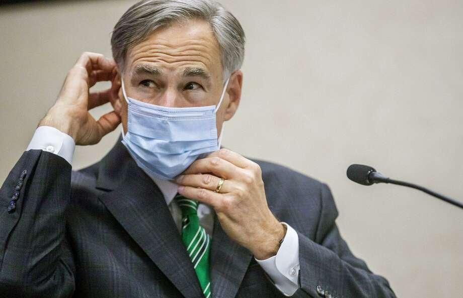 Texas Gov. Greg Abbott adjusts mask during Tuesday update on coronavirus in Texas. (Ricardo Brazziell/Austin American-Statesman/TNS) Photo: Ricardo Brazziell, MBR / TNS / Austin American-Statesman