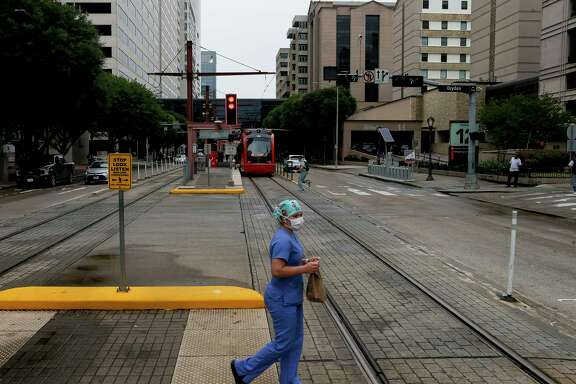 A woman uses the crosswalk on Dryden Road in the Medical Center on Monday, June 22, 2020, in Houston. Texas Medical Center executives and Harris County health officials predict that as COVID-19 cases and hospitalizations continue to rise, the Houston area will effectively return to stay-at-home status as many businesses close due to sick employees.