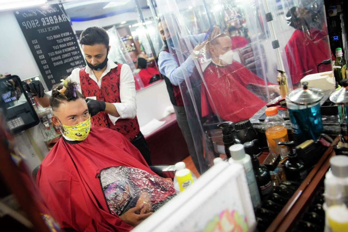 Brian Nieh wears a protective mask as he receives a haircut at Ace of Cuts barbershop, Monday, June 22, 2020, in the Manhattan borough of New York. For the first time in three months, New Yorkers will be able to dine out, though only at outdoor tables. Shoppers can once again browse in the city's destination stores. Shaggy heads can get haircuts. Cooped-up kids can finally climb playground monkey bars instead of apartment walls. Office workers can return to their desks, though many won't yet. (AP Photo/John Minchillo)