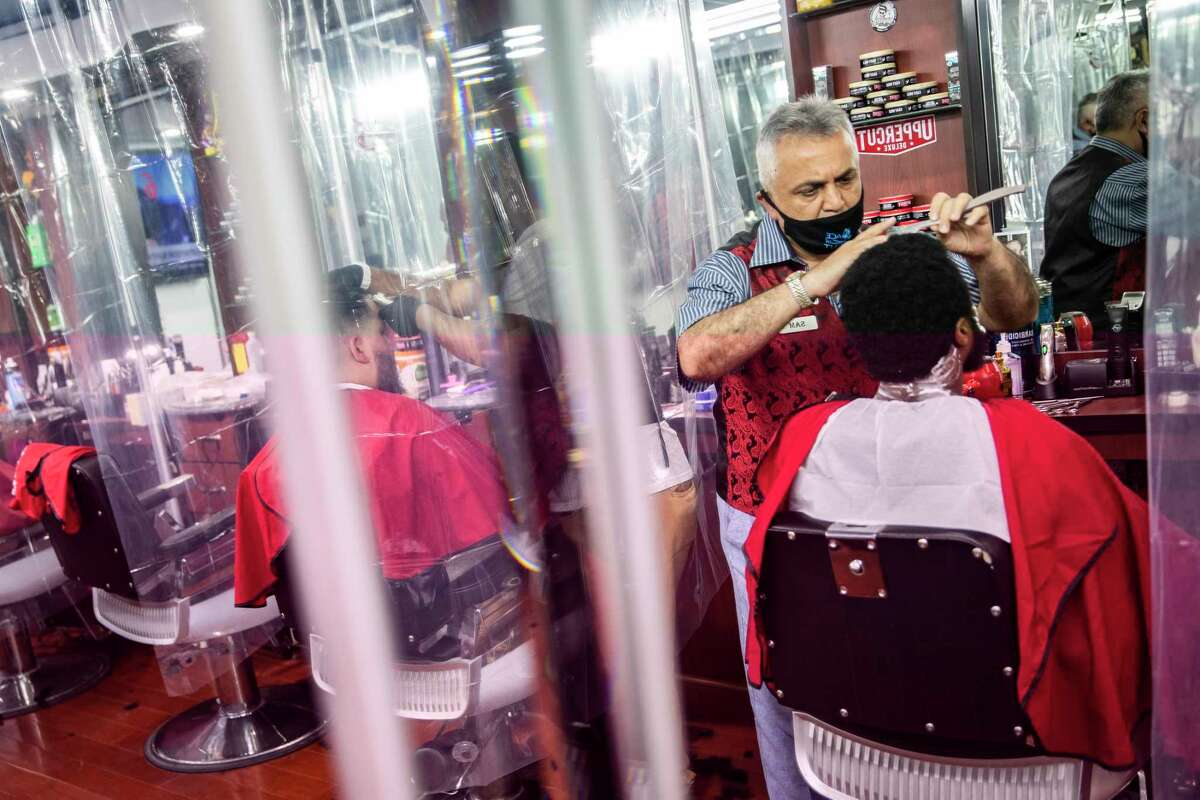 Sam Shamuelov wears a protective mask as he gives a haircut to a customer at Ace of Cuts barbershop, Monday, June 22, 2020, in New York. For the first time in three months, New Yorkers will be able to dine out, though only at outdoor tables. Shoppers can once again browse in the city's destination stores. Shaggy heads can get haircuts. Cooped-up kids can finally climb playground monkey bars instead of apartment walls. Office workers can return to their desks, though many won't yet. (AP Photo/John Minchillo)