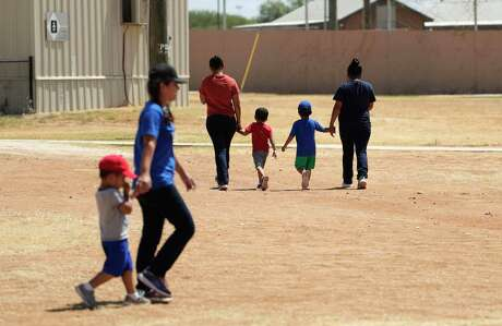 Immigrants seeking asylum hold hands as they walk across the South Texas Family Residential Center in Dilley last year. The facility has not done enough testing for coronavirus cases, two visiting U.S. House members said Monday. (AP Photo/Eric Gay)