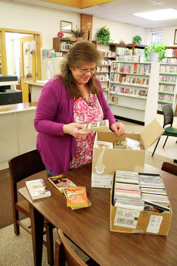 After months of being closed because of the coronavirus, Walton Erickson Public Libraryisopened for curbside service. Staff have beensanitizing materialand surfaces, careful to follow CDC and health department guidelines,in preparation for Phase 3 of the library's reopening plan.Above, staff pack books to sendoverseas to military personnel in 2016. (Pioneer file photo)