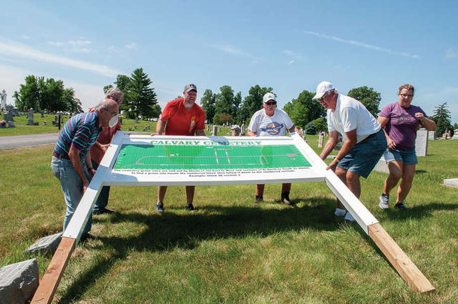 Calvary Cemetery board members help install a sign Monday to help visitors find gravesites. They include Ray DePauw (from left), Jerry Denight, Chad Myers, Don Schmidt, Ken Zumbahlen and Lorratta Myers. Photo: Darren Iozia | Journal-Courier