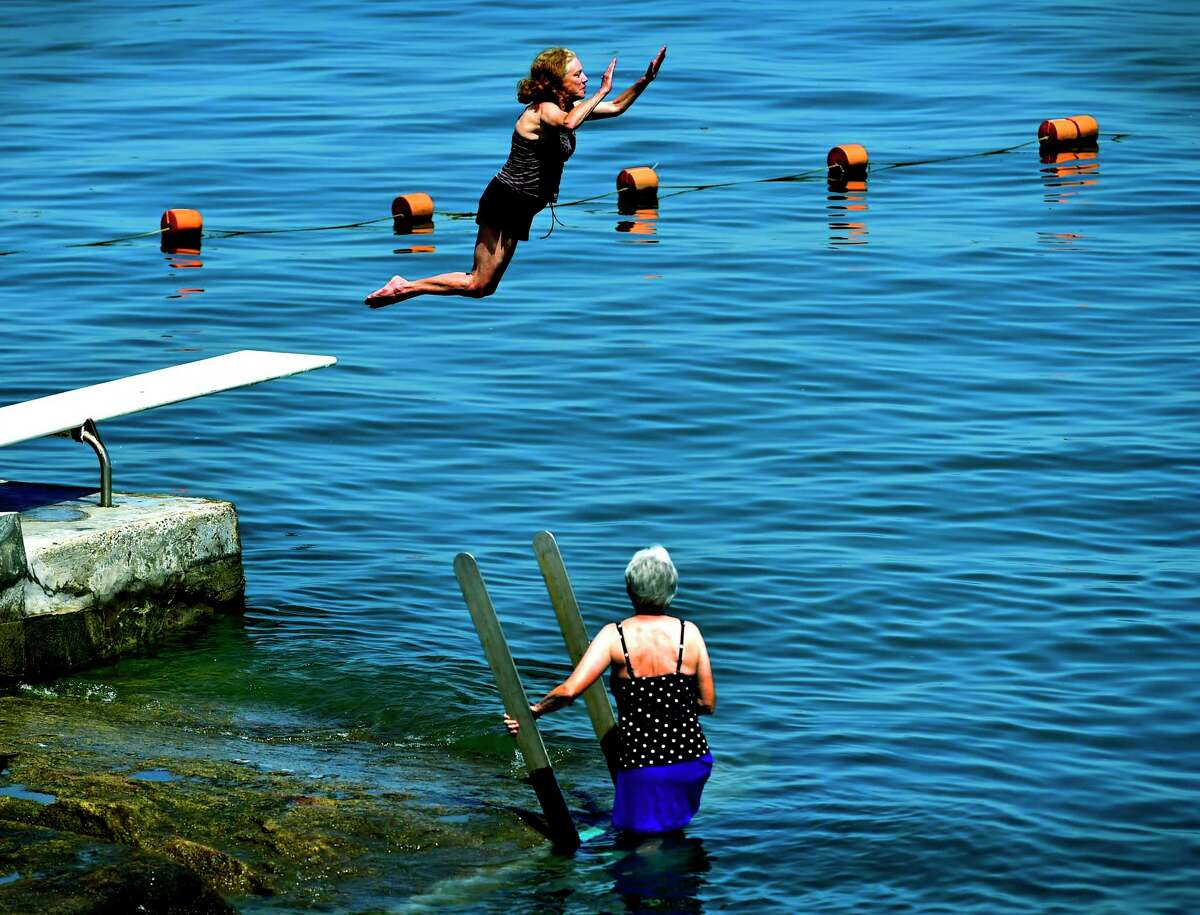 Nancy Domark of Branford takes a leap June 22, 2020 off the Indian Neck diving board into the Long Island Sound with a cool splash at the Linden Shores District Pebbly Beach on in Branford as friend Jane Zilinskas of Branford observes, right. If the hot weather persists, abnormally dry conditions in half the state could spread.